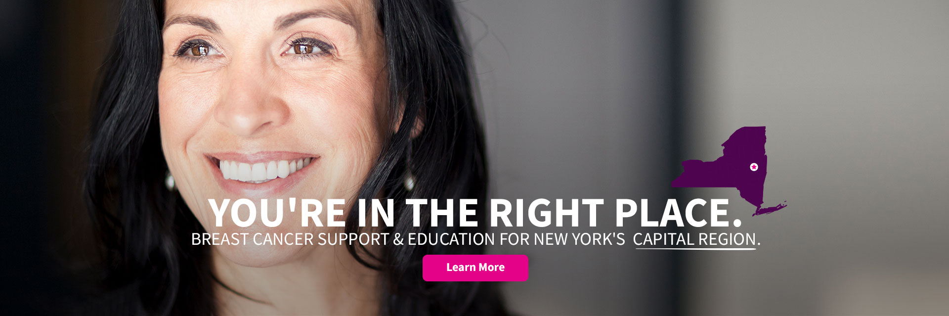 Woman smiling in support of breast cancer education