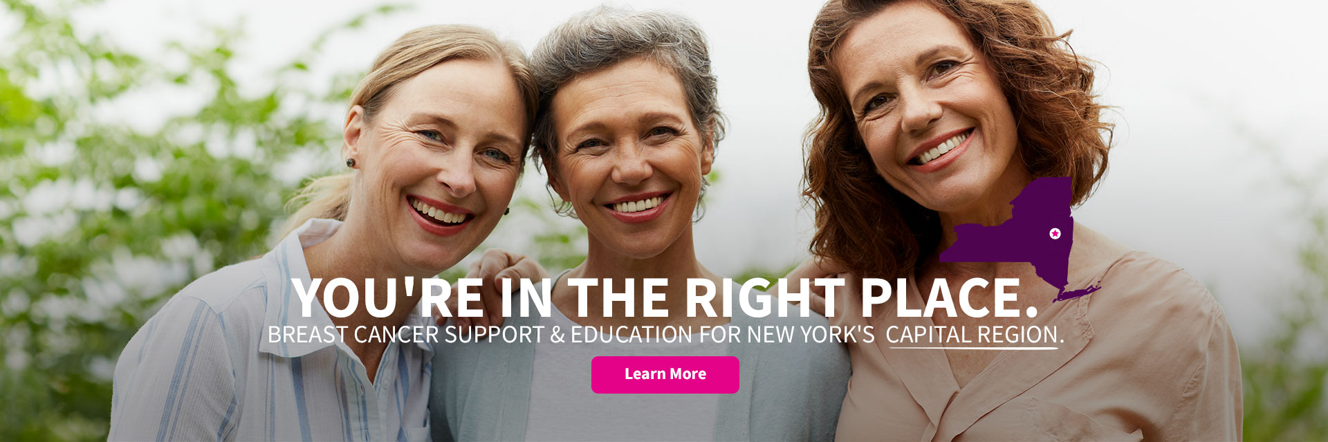 Three women smile in support of breast cancer education